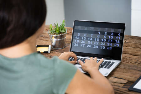 Cropped Image Of Businesswoman Using Laptop At Desk In Office