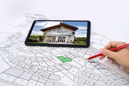 Hand met potlood over kadasterkaart Nieuwe tablet met huisfoto Stockfoto