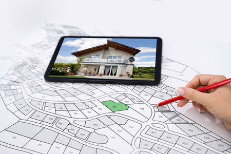 Ręka trzymająca ołówek nad mapą katastru Nowy tablet ze zdjęciem domu Zdjęcie Seryjne