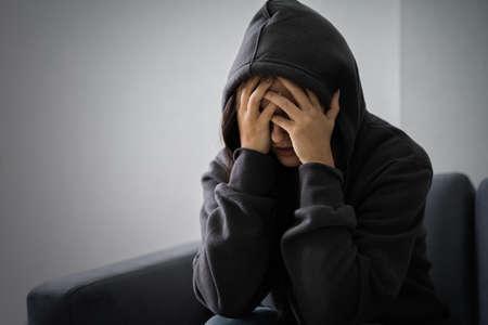 Junge depressive Frau im Hoodie sitzt auf dem Sofa zu Hause