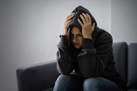 Young Depressed Woman In Hoodie Sitting On Sofa At Home