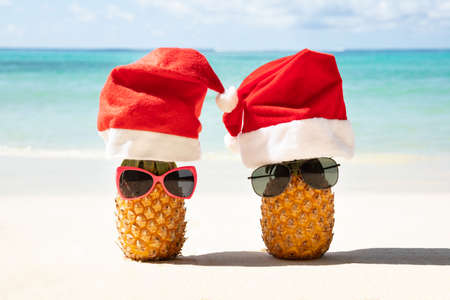 Close-up Of Santa Hats And Sunglasses Over The Two Pineapples On Sand At Beach Stockfoto