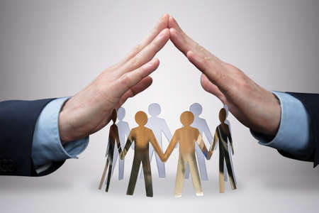 Close-up Of Businessmans Hand Protecting The Circle Of White Paper Cut-out Figures On Gray Background