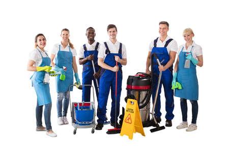 Grupo diverso de conserje profesional de pie con su equipo de limpieza contra el fondo blanco.