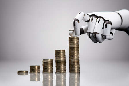 Close-up Of A Robotic Hand Placing The Coin Over The Stack Against Gray Background