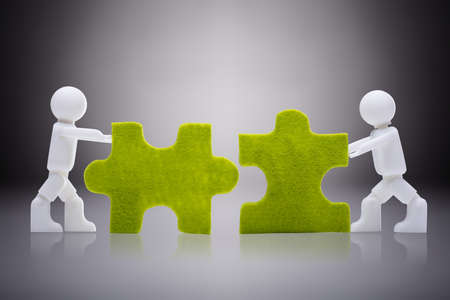 Two White Human Figures Joining The Green Jigsaw Pieces On Gray Background