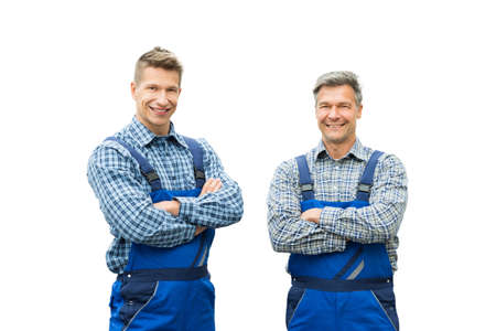 Smiling Portrait Of Two Male Handymen With Arms Crossed Looking At Camera Against White Background Stock Photo