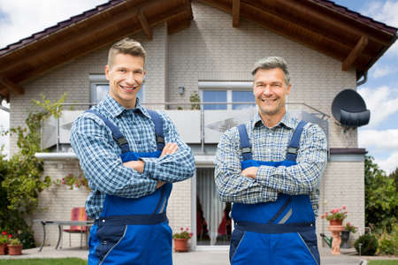 Confident Smiling Portrait Of Two Male Handymen Looking At Camera Standing In Front Of House