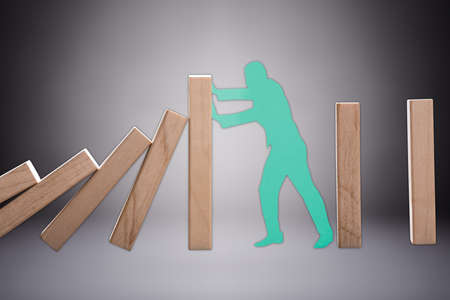 Green Cut Out Human Figure Stopping The Wooden Domino To Fall Against Grey Background Imagens