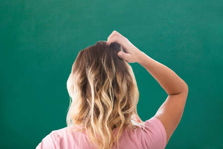 Rear View Of Blonde Young Woman Scratching Her Head Against Green Background