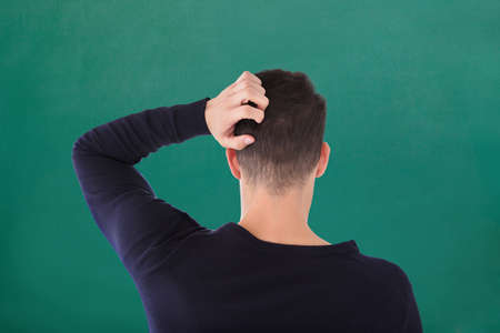 Rear View Of Young Man In Blue T-shirt Scratching His Head Against Green Background 写真素材