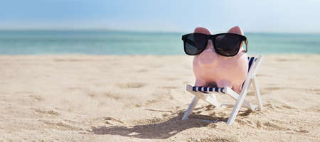 Pink Piggybank Wearing Eyeglasses On Deck Chair Over The Sandy Beach Reklamní fotografie