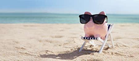 Roze spaarpot met bril op ligstoel boven het zandstrand Stockfoto