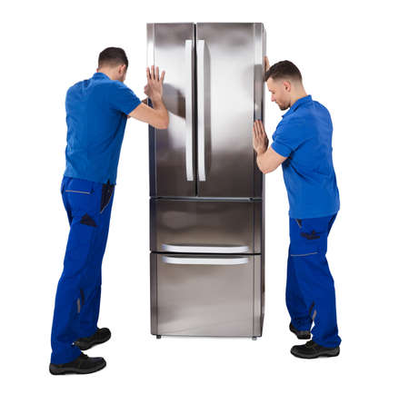 Rear View Of Two Male Movers Placing The Sliver Refrigerator Against White Background