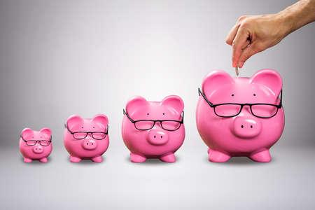 Mano d'uomo inserendo la moneta in un grande salvadanaio rosa con occhiali contro sfondo grigio