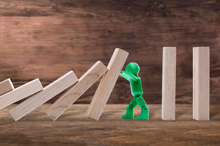 Side View Of A Green Plastic Figure Stopping The Wooden Domino Effect On Plank Imagens