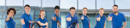 Portrait Of A Smiling Diverse Young Janitors With Cleaning Equipment Against Window Glass