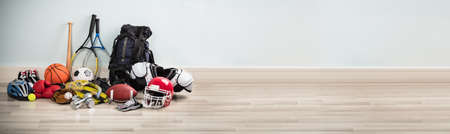 Different Type Of Sports Equipment On Wooden Desk Against White Wall Stockfoto