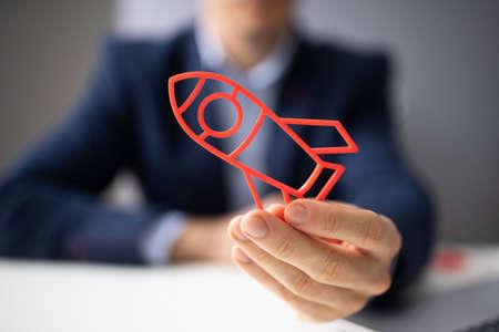 Close-up Of A Businesspersons Hand Flying Rocket Reklamní fotografie