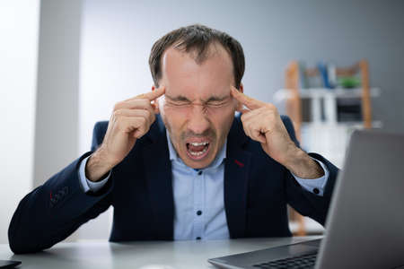 Stressed Young Businessman Screaming In The Office