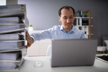 Businessperson Pushing Paper Documents Away And Working With Digital Documents On Computer Instead