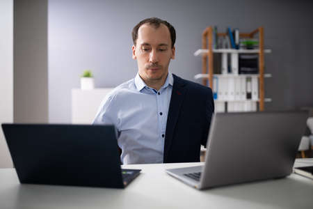 Businessperson Doing Multitasking Work On Two Laptops At Workplace