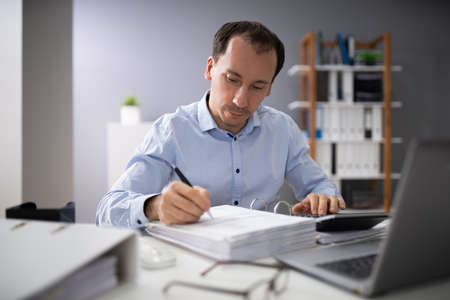 Over The Shoulder View Of Businessman Calculating Invoices Using Calculator Reklamní fotografie