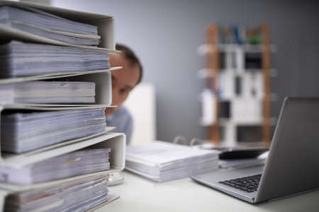 Close-up Of A Businessman Hiding Behind The Stack Of Folders On Desk At Workplace