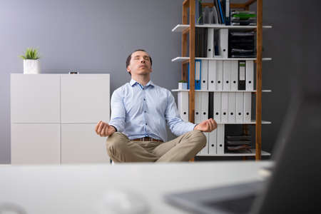 Young Businessman Doing Yoga Behind Desk In Office