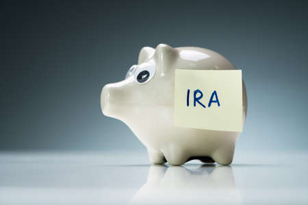 A White Piggy Bank On A Reflective Desk With Ira Text On Adhesive Note Stock fotó