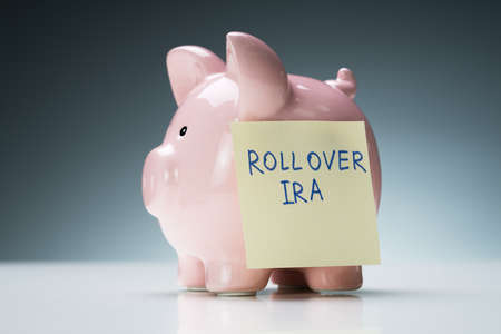 Close-up Of Rollover Ira Text On Sticky Note With Pink Piggy Bank Over White Desk Stock Photo