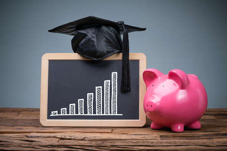 Close-up Of Pink Piggybank In Front Of Blackboard Showing Graph Stock fotó - 133704131