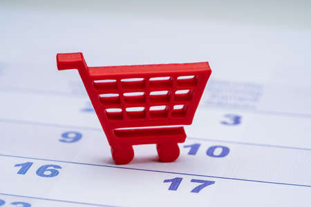 Red Shopping Trolley Toy Over The Calendar Date Reklamní fotografie