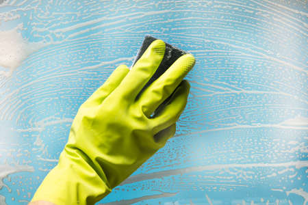 Person Wearing Green Gloves Cleaning Soap Suds Over Glass Window With Sponge