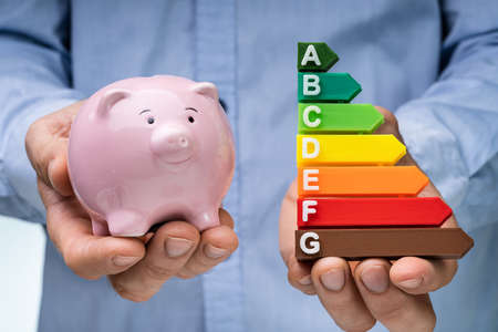 Mid Section Of A Man's Hand Holding Pink Piggybank And Colorful Energy Efficiency Graph Stock fotó - 133704141