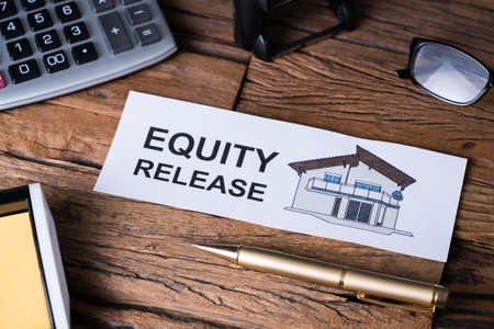 Overhead View Of Equity Release Text On Paper With A Colored House Near Office Supplies Banque d'images