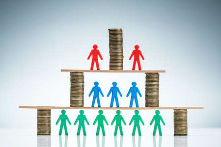 Corporate Hierarchy Concept With Stacked Of Coins And Colorful Human Figures Against Colored Background Stock fotó