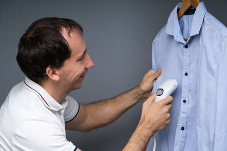 Close-up Of A Man Steaming Blue Shirt Using Electric Steamer Stockfoto