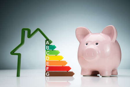 Green House Energy Efficiency Graph Near The Pink Piggybank On White Desk Against Blue Background Stock fotó - 133704460