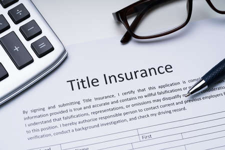 Title Insurance Form Near Calculator And Glasses 스톡 콘텐츠