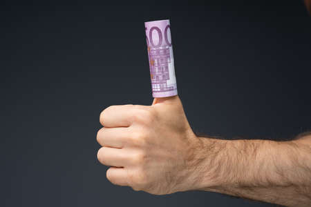 Mid Section Of A Man's Hand Showing Rolled Up 500 Euro Notes Over His Thumb Stock fotó - 133704472