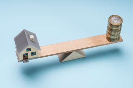 An Overhead View Of Miniature House And Coin Stacks On Wooden Seesaw Against Blue Background Reklamní fotografie
