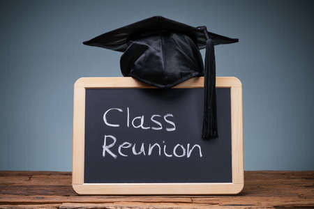 Black Graduation Hat Over The Slate With Written Text Class Reunion On Wooden Desk Stock fotó