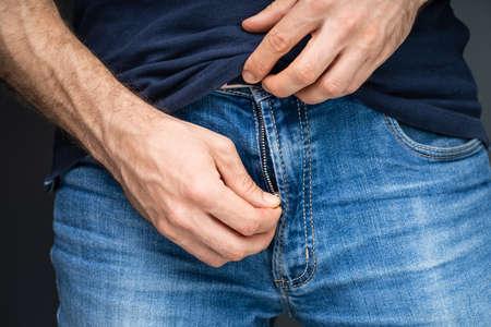 Close-up van de hand van een man die zijn blauwe spijkerbroek openritst Stockfoto