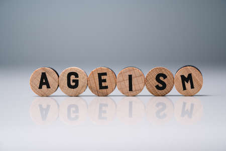 Ageism Text On Round Wooden Blocks Over Reflective White Desk Stok Fotoğraf