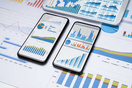 Close-up Of Financial Graphs On Screens Of Multiples Smartphones On Desk Stock fotó - 133704906