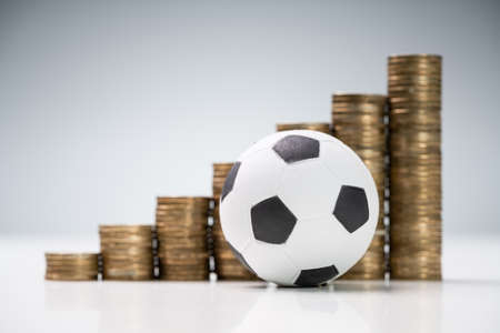 Soccer Ball In Front Of Golden Coin Stacks On White Desk Against Gray Background