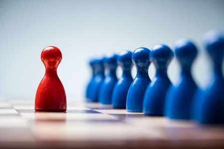 Rote Bauern vor blauen Bauern auf dem Schachbrett vor blauem Hintergrund Standard-Bild