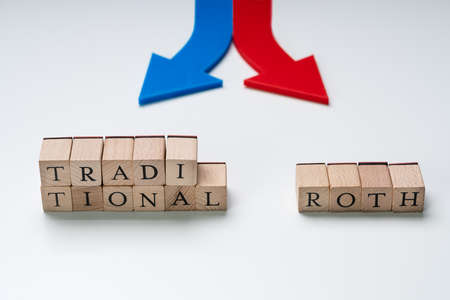 Red And Blue Directional Arrows Showing Traditional And Roth Ira Options On Wooden Blocks