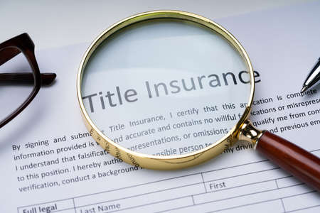 Magnifying Glass Over Title Insurance Form On Table